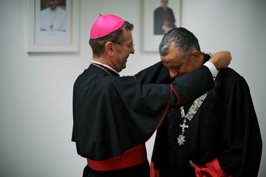 Mons. Ivan Šašku uručuje rektoru rektorski lanac, znak rektorske časti.